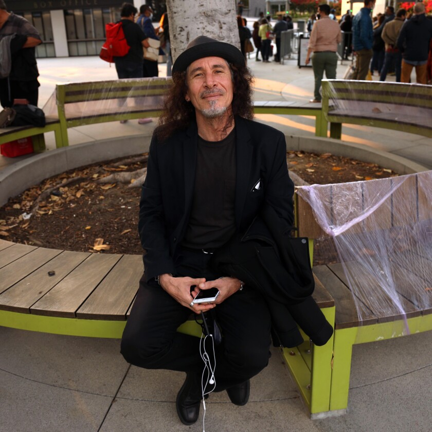 A man in a hat holds his phone as he poses for a photo seated on a bench.