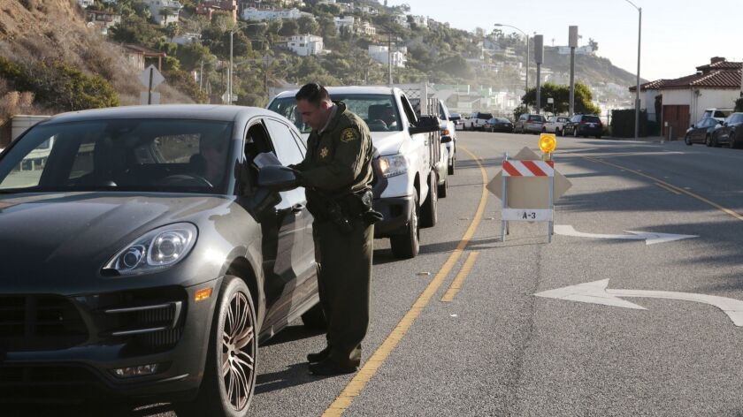 Law enforcement officials check the IDs of residents returning to Malibu. The evacuation order has been lifted for Malibu from Carbon Canyon to Webb Way.