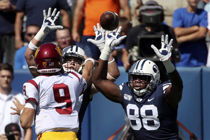 BYU players pressure USC quarterback Kedon Slovis during the first half of Saturday's game.