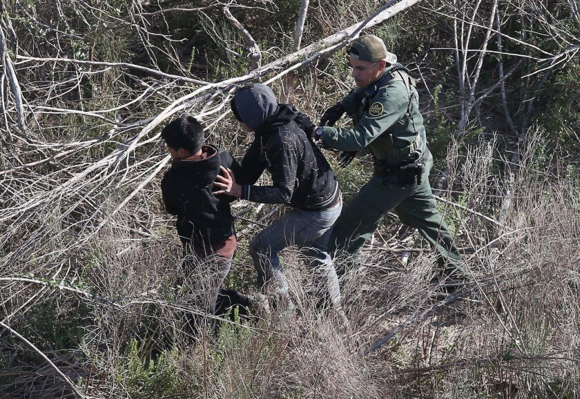 A U.S. Border Patrol agent detains juvenile undocumented immigrants near the U.S.-Mexico border in December 2015 at La Grulla, Texas. The number of unaccompanied minors crossing the border from Central America has surged in recent months.