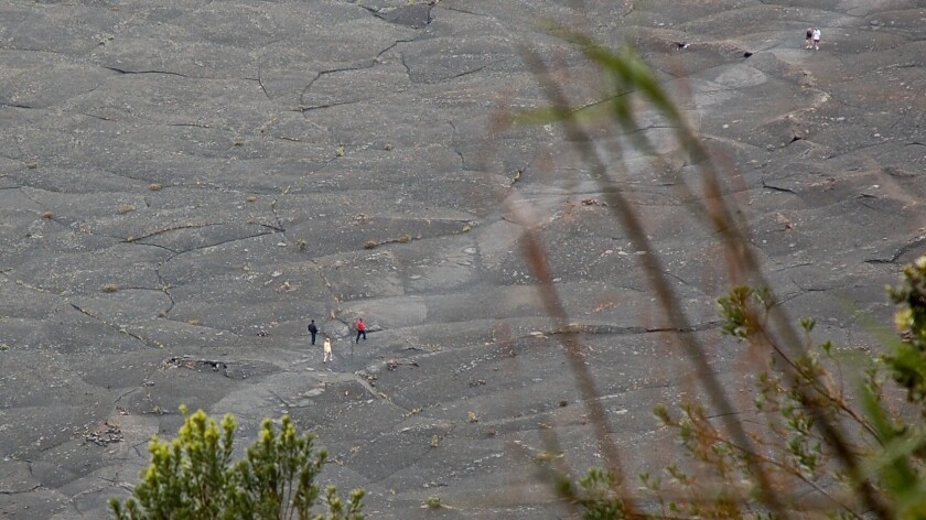 Tiny to the eye, these hikers are on the Kilauea Iki Trail, inside a caldera that's part of Hawaii Volcanoes National Park on the Big Island of Hawaii.
