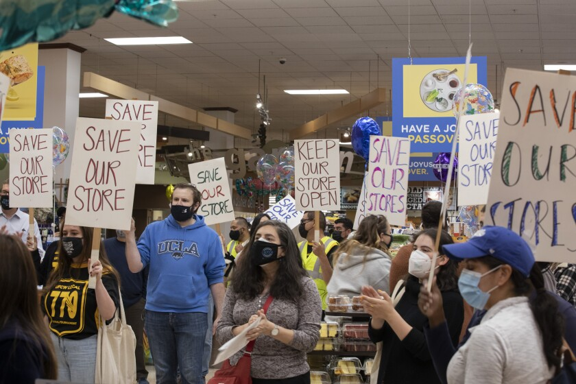 Protesters inside a supermarket with signs that say Save Our Store and Keep Our Store Open