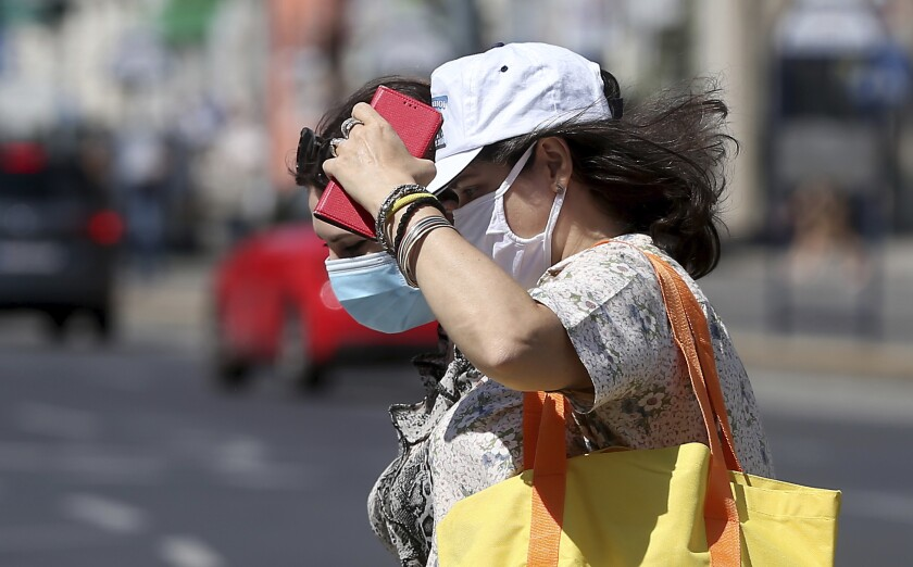 """FILE -- In this Wednesday, Aug. 19, 2020 photo people wear face masks as they cross a street in Vienna, Austria. Austria's Chancellor Sebastian Kurz says his country is seeing the start of a """"second wave"""" of coronavirus infections. He is appealing to his compatriots to comply with newly reinforced rules to keep down infections. (AP Photo/Ronald Zak, file)"""