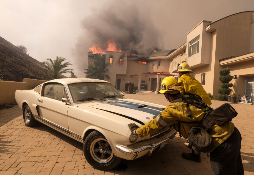 FILE - In this Friday, Nov. 9, 2018 file photo, firefighters push a vehicle from a garage as the Woo