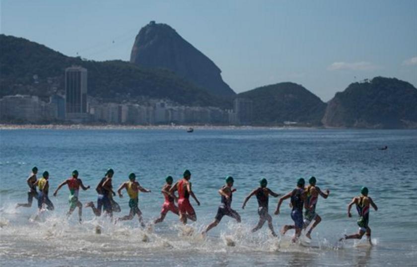 Triatletas entran al agua al comienzo de una competencia en Río de Janeiro, Brasil. Se espera la presencia de cientos de miles de turistas para los Juegos Olímpicos de Río, aunque la preocupación por el virus del zika podría ahuyentar a algunos. (AP Photo/Felipe Dana, File)