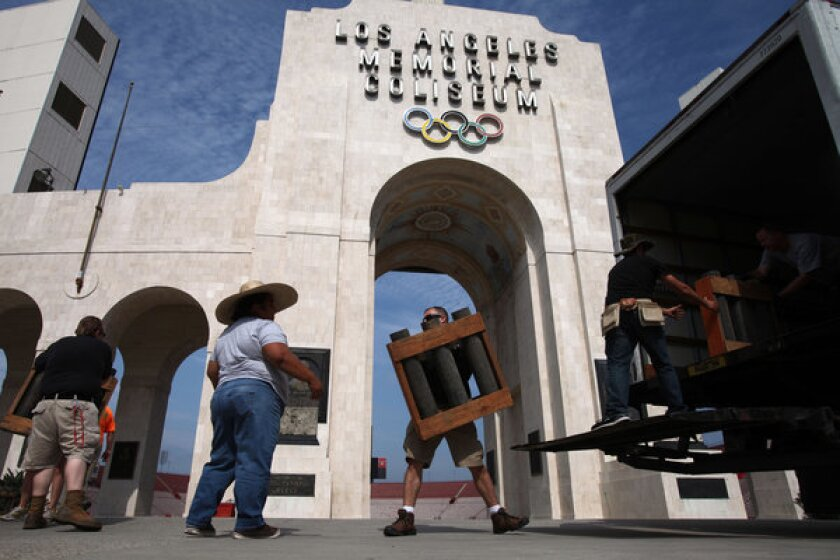 Pyrotechnic workers set up for this year's Fourth of July fireworks show at the Los Angeles Memorial Coliseum.