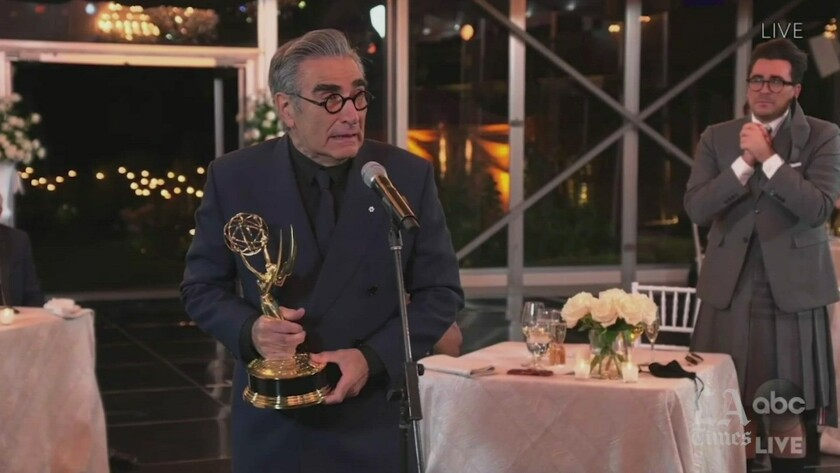 Eugene Levy accepts his Emmy while his son, Daniel, watches.