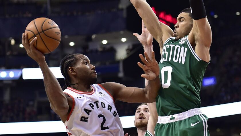 Boston Celtics forward Jayson Tatum (0) and forward Gordon Hayward (20) pressure Toronto Raptors forward Kawhi Leonard (2) during the second half on Friday.