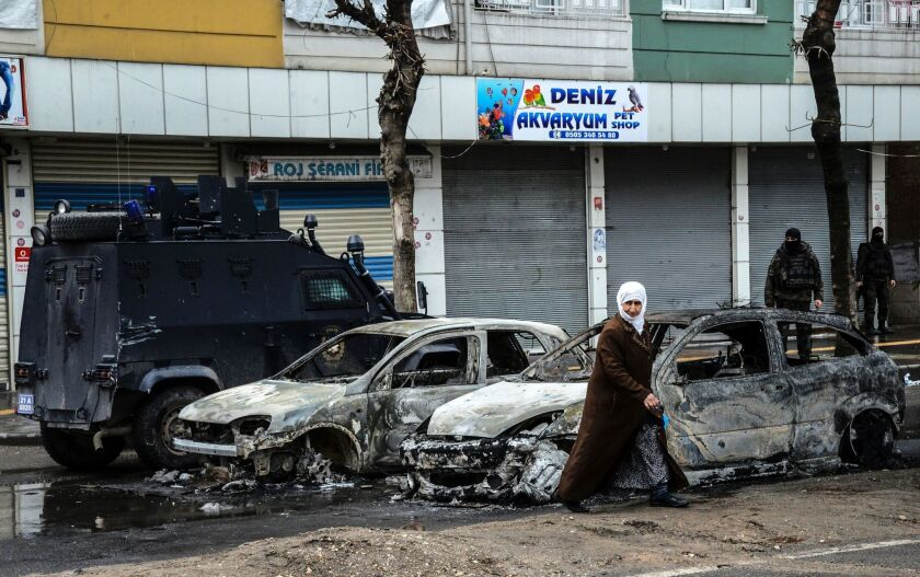 People walk past destroyed vehicles as they leave their houses during clashes in central Diyarbakir on March 15, 2016.