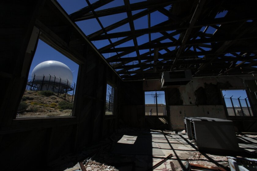 Nearly a dozen abandoned buildings at the former site of the Laguna Mountain Air Force Base will be removed. An FAA radar facility, seen through the window of a building, will remain. Peggy Peattie • U-T