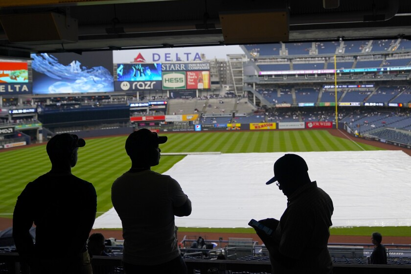 Fans wait for the rain to stop before a baseball game between the New York Yankees and the New York Mets at Yankee Stadium, Friday, July 2, 2021, in New York. (AP Photo/Frank Franklin II)