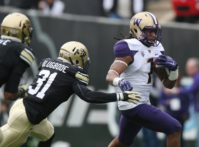 In this Saturday, Nov. 1, 2014, photo, Washington running back Shaq Thompson, right, eludes a tackle attempt by Colorado linebacker Kenneth Olugbode during an NCAA college football game in Boulder, Colo. Olugbode will be back on the gridiron when Colorado hosts Stanford on Saturday, Nov. 7, after m