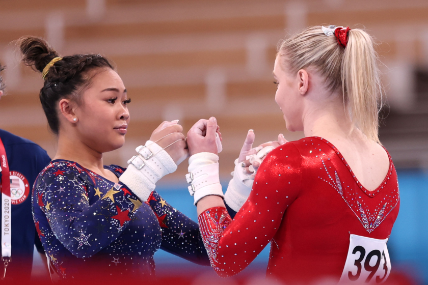 U.S. gymnasts Sunisa Lee, left, and Jade Carey fist bump during the qualification round at the Tokyo Olympics on Monday.