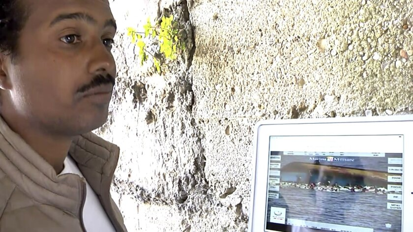 In this image taken from video, Mohammed Ali, from Sudan, is interviewed as he is shown an Italian Navy video of the capsizing of a boat he was on during an interview with the Associated Press in Siculiana, in Sicily, Italy, Friday, May 27, 2016. Ali, who survived the capsizing of the vessel, said