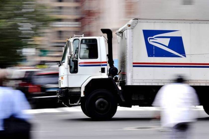 A U.S. Postal Service truck, in focus against a blurred background, drives on a city street