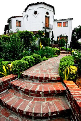 """By Debra Prinzing Mae Brunken wanted a home with a past. The interior designer and set decorator ultimately found her period piece high in the hills of Hollywood: a 1927 Spanish Colonial Revival that starred as the home of Phyllis Dietrichson (Barbara Stanwyck) in Billy Wilder's """"Double Indemnity."""" As principal of Mae Brunken Design, Brunken likes to create spaces """"around a character and what that character would love."""" In renovating the white stucco-and-red-tile-roofed """"Double Indemnity"""" house, she channeled the character of a glamorous movie star of the 1930s and '40s. """"I wanted to restore the house and have fun furnishing it as a part of the Hollywood era,"""" she says. To blend two styles -- Deco interiors and Spanish architecture -- Brunken couldn't interpret either too purely. Instead, she used vivid Deco colors and glossy finishes to brighten the home's traditional terra cotta floors, stark white stucco walls and exposed beams. """"I like my environments to be modern-day and a little playful,"""" she says. """"I love fresh and happy color. I want to mix different periods and allow the pieces to play together."""""""