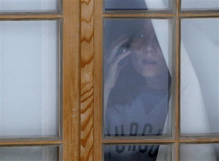 French actress Emmanuelle Seigner, the wife of film director Roman Polanski, peers out of the window as she holds a cell phone in her hand, at the chalet in Gstaad, Switzerland, Friday, Dec. 4, 2009. Roman Polanski's family waited inside the director's Alpine chalet Friday as Swiss authorities worked out the last-minute details of his transfer to house arrest. (AP Photo/Michel Euler)