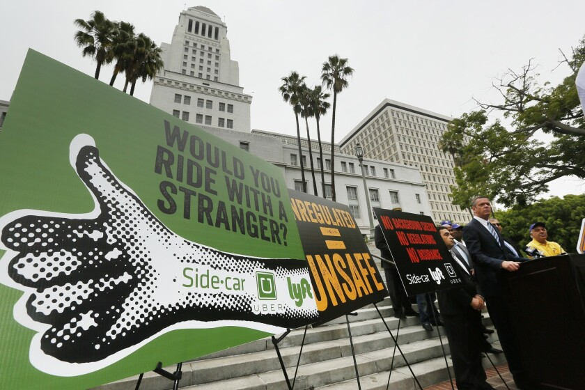 Taxi drivers protest ride-share apps outside of Los Angeles City Hall. The City Council is considering appealing a recent state decision to allow the companies to operate.