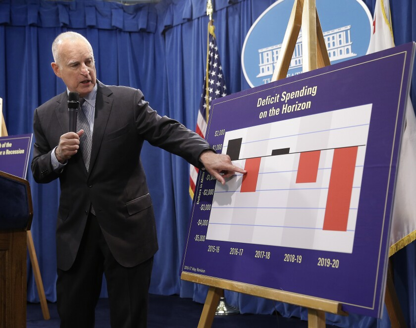 California Gov. Jerry Brown gestures to a chart showing that budget deficits usually follow balanced