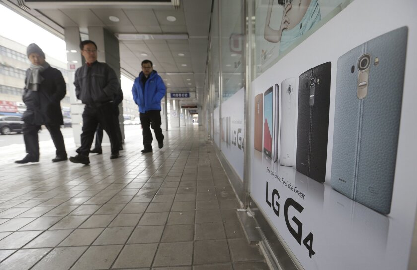People pass by banners advertising LG Electronics' G4 smartphone at a shopping mall in Seoul, South Korea, Tuesday, Jan. 26, 2016. LG Electronics reported an unexpected loss in the final quarter of 2015 as its smartphone business struggled. (AP Photo/Ahn Young-joon)
