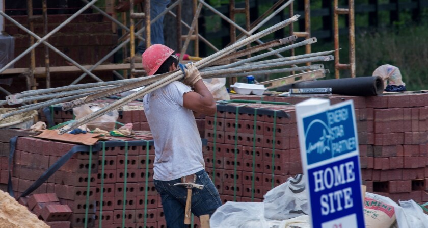 A worker carries scaffolding poles on a home site in Virginia.
