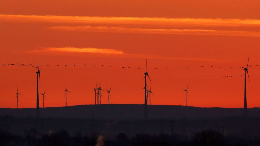 FILE - In this March 28, 2017 file photo a swarm of birds flies past wind turbines just before sunri