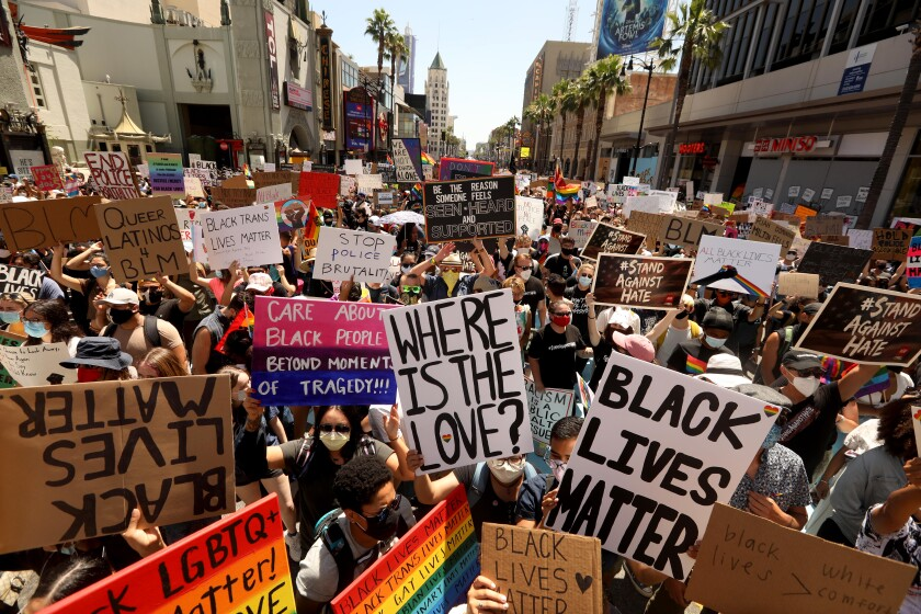 Marchers raise signs as they crowd Hollywood Boulevard during the All Black Lives Matter march