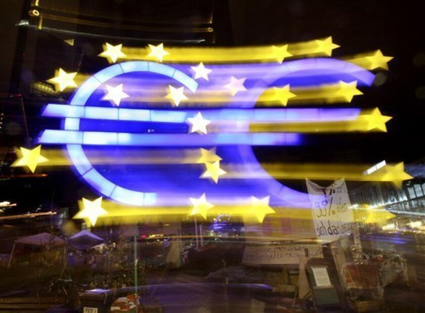 The Euro sculpture at the European Central Bank is photographed with long exposure and moving camera in Frankfurt, Germany, Sunday, Jan. 1,2012. (AP Photo/Michael Probst)