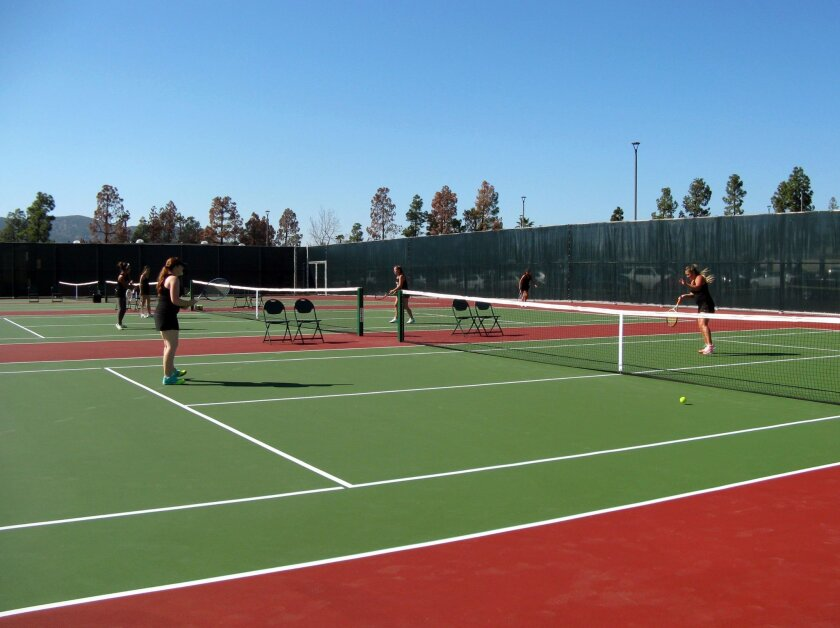 Members of the Grossmont College women's tennis team play on the campus's new tennis courts. The courts, which are designed to wear longer and clear away rain water better, are open to the public.