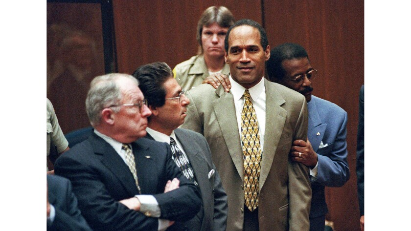 Oct. 3, 1995: Attorney Johnnie Cochran Jr., right, clutches his client O.J. Simpson as a not guilty verdict is read. At left is F. Lee Bailey, and second from left is Robert Kardashian.