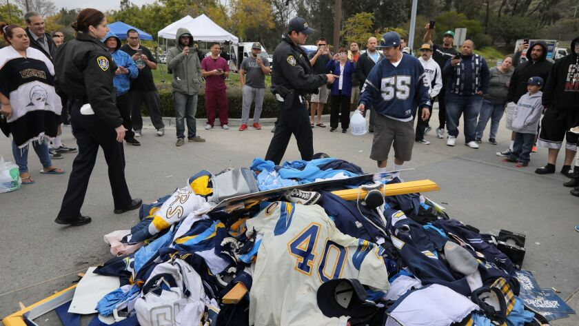 At Chargers headquarters on Murphy Canyon Road two SDPD Officers move in quickly to stop angry Chargers fan Mercury Hornbeek from pouring bleach on a pile of discarded Chargers gear in front of the