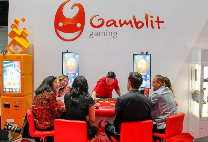 A group of people play Gamblit Poker Live at the Gamblit booth during the Indian Gaming Convention on Thursday in San Diego, California. (Eduardo Contreras/Union-Tribune)