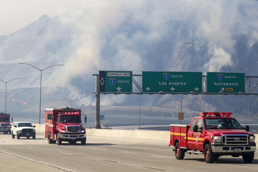 Smoke rises in the Newhall Pass during the Saddleridge fire.
