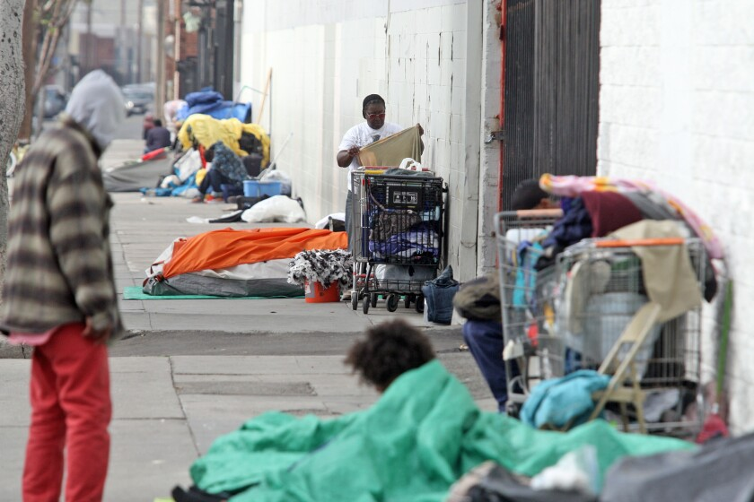 Annie Moody adjusts belongings next to her tent on Towne Avenue at 6th Street in Los Angeles.