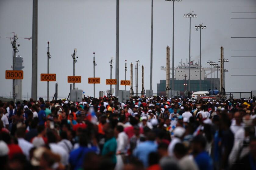 """Miles de espectadores observan mientras el portacontenedores chino """"Cosco Shipping Panama"""" se prepara para cruzar la nueva esclusa de Agua Clara, parte del ampliado Canal de Panamá, cerca de la ciudad portuaria de Colón, Panamá, la mañana del domingo 26 de junio de 2016. (AP Foto/Moisés Castillo)"""