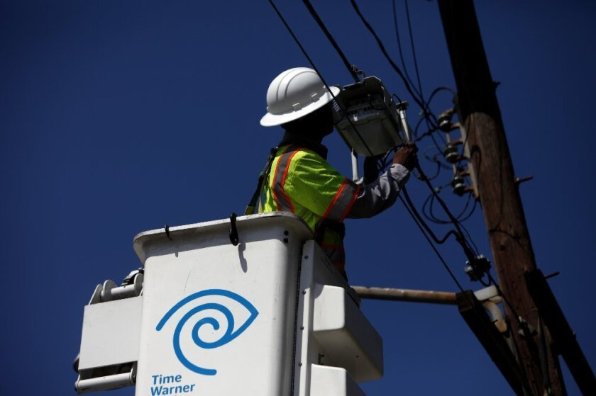 Morris Hibbitt, a field technician for Time Warner Cable Inc., cleans and checks the connection for a Wi-Fi hotspot in Manhattan Beach in August 2013.