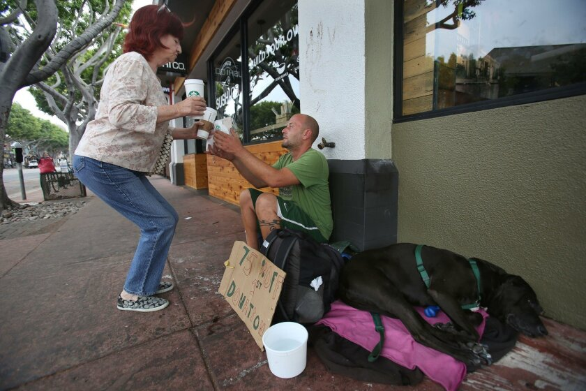 Jason Goodman reaches up to take a coffee and sandwich from local resident Fay Bowermaster outside the Starbuck's on Fifth and Robinson avenues in Hillcrest Thursday morning. Goodman said he wishes he would rather work than panhandle, but local businesses won't hire him. A security firm that will f