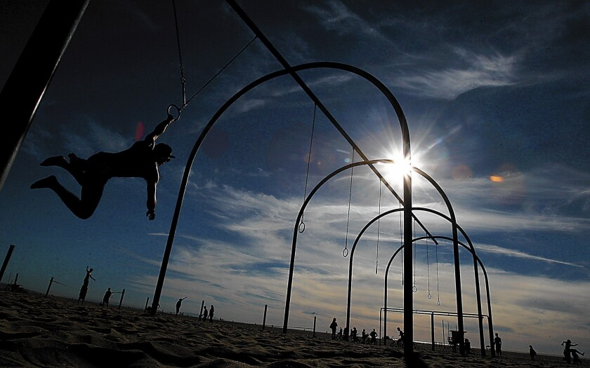 Matias Letelier swings on a ring apparatus on a summer-like day in Santa Monica. The Southland's weather is expected to remain dry through the last days of the year.