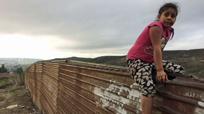 Sol, age 7, plays on the border wall, which stretches for miles into the western horizon.