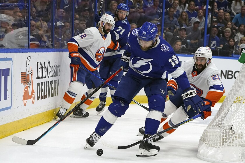 Tampa Bay Lightning center Barclay Goodrow (19) moves the puck away from New York Islanders left wing Otto Koivula (21) during the second period in Game 5 of an NHL hockey Stanley Cup semifinal playoff series Monday, June 21, 2021, in Tampa, Fla. (AP Photo/Chris O'Meara)