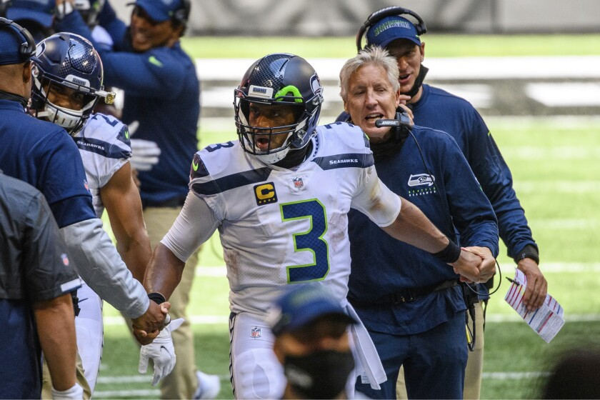 FILE- In this Sunday, Sept. 13, 2020, file photo, Seattle Seahawks head coach Pete Carroll, right, shakes hands with quarterback Russell Wilson (3) on the sideline during the second half of an NFL football game against the Atlanta Falcons in Atlanta. The= Seahawks have had a nasty habit of starting slowly. If their debut at Atlanta last weekend is any indication, Carroll and Wilson have the motors revving from the jump. (AP Photo/Danny Karnik, File)