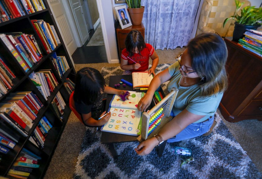 Maggie Tamayo worked with two daughter, Amelia, 6, and Esperanza, 8, on homeschool assignments in October.