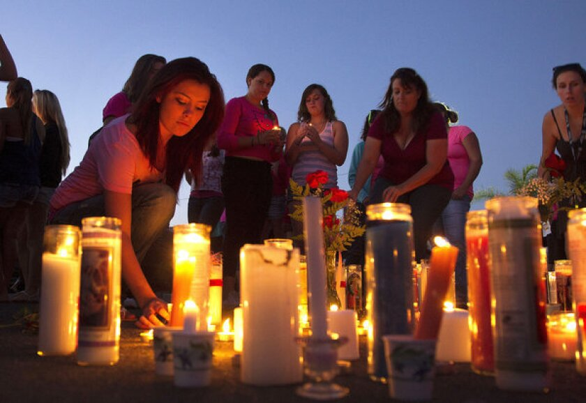 Athena Stewart lights a candle during a vigil at El Capitan High School in Lakeside, Calif. Missing teen Hannah Anderson is a student at the school.