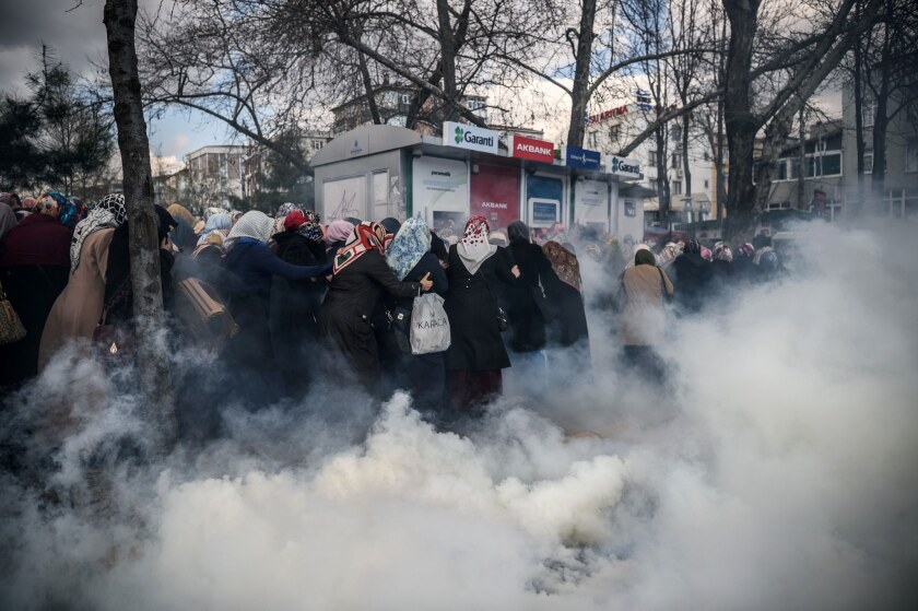 Smoke rises near a group of women as Turkish anti-riot police officers use tear gas to disperse supporters in front of the headquarters of the Turkish daily newspaper, Zaman, in Istanbul after Turkish authorities seized the headquarters in a midnight raid.