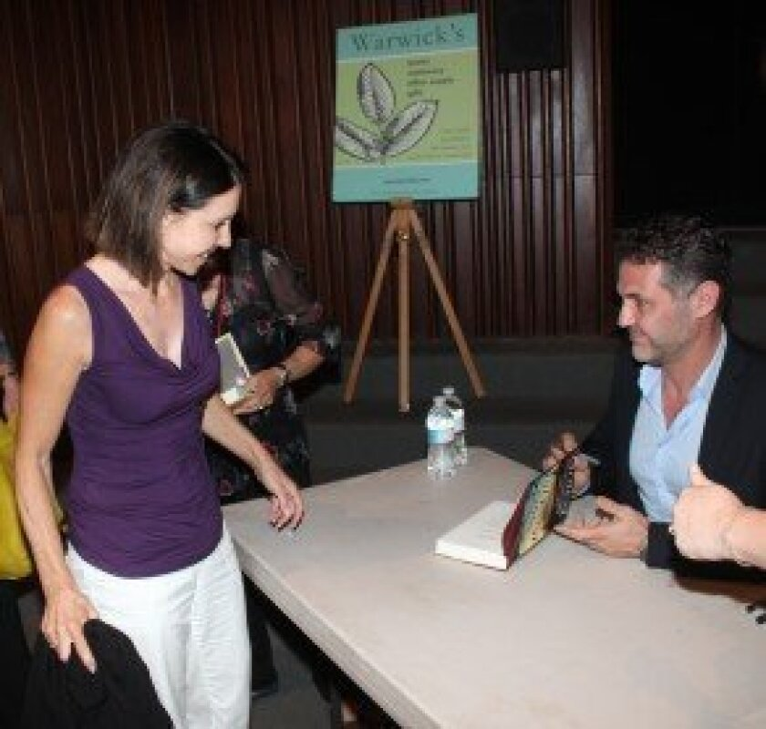 Khaled Hosseini signs copies of his new book, 'And the Mountains Echoed' for attendees at Warwick's sold-out author event at the Museum of Contemporary Art in La Jolla.