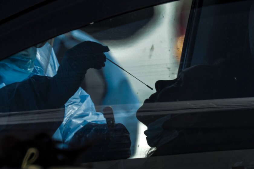 A worker takes a sample at a drive-through testing site in Victorville.