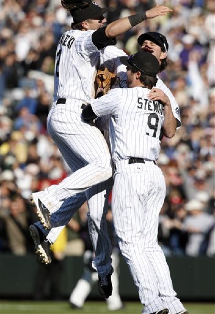 Colorado Rockies shortstop Troy Tulowitzki, left, joins third baseman Ian Stewart, front right, and first baseman Todd Helton after the Rockies' 9-2 victory over the Milwaukee Brewers to clinch a spot in the National League baseball playoffs, in Denver on Thursday, Oct. 1, 2009. (AP Photo/David Zalubowski)