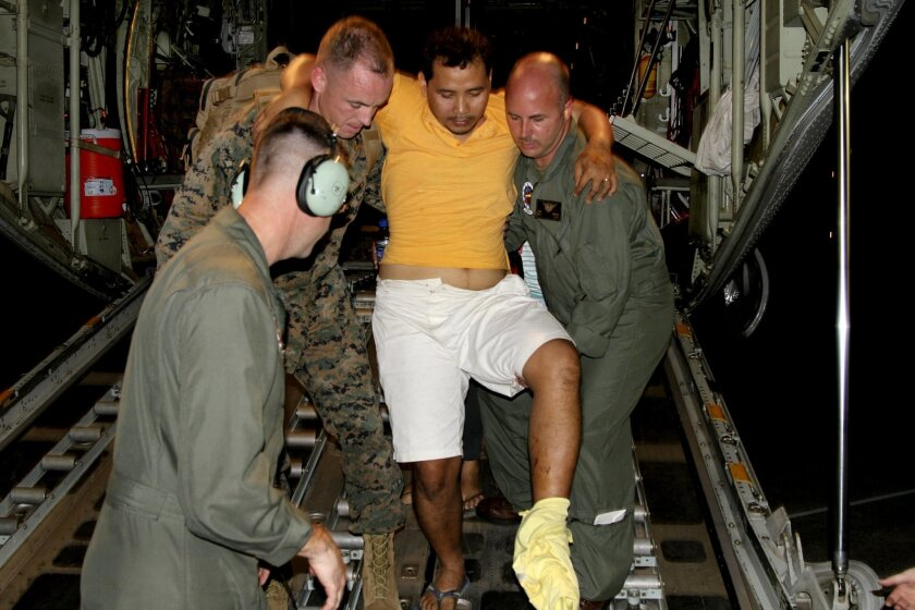 U.S. Marines carry an injured Filipino man off the back of a KC-130J Super Hercules at Villamor Air Base, Manila, the Philippines, Nov. 11, 2013. Defense Secretary Chuck Hagel directed the U.S. Marines to provide humanitarian relief at the request of the government of the Phillippines. (DOD)