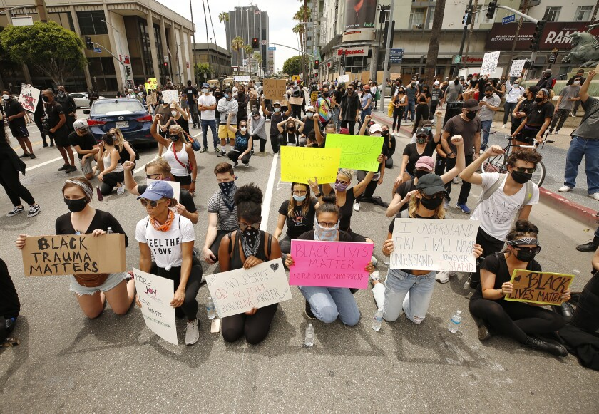 Protesters take a knee in front of LAPD officers at Vine Street in Hollywood.