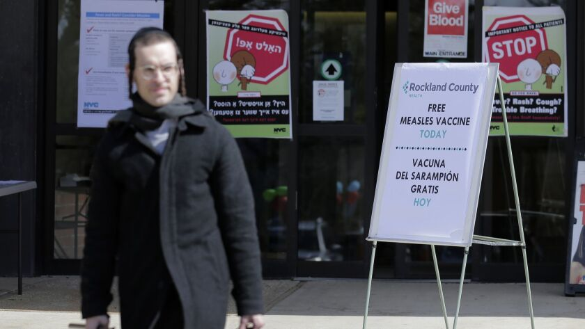 FILE - In this March 27, 2019 file photo, signs about measles and the measles vaccine are displayed